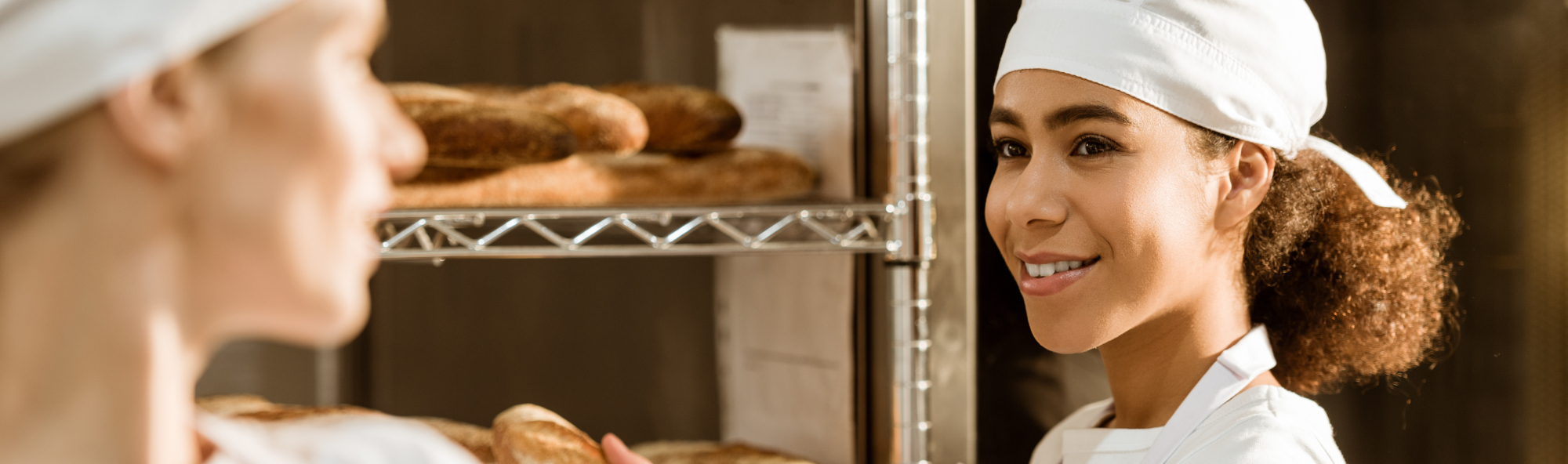 happy young female bakers working at baking manufacture